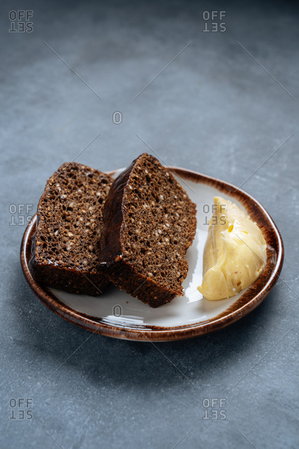 From above of slices of rye bread with bran on plate with slice of butter on grey table