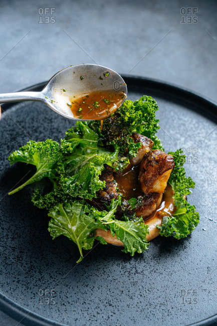 From above of fried meat served with fresh green lettuce leaves on black plate pouting brown sauce with spoon