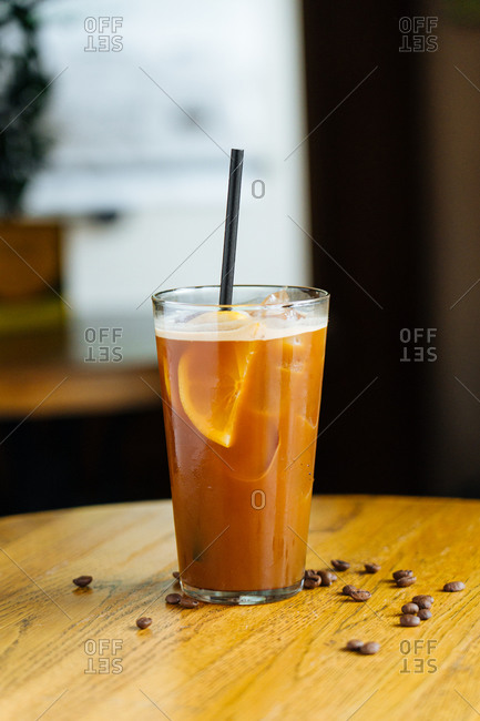 Cold coffee with ice and slices of lemon in modern glass with tube on wooden table with coffee bean