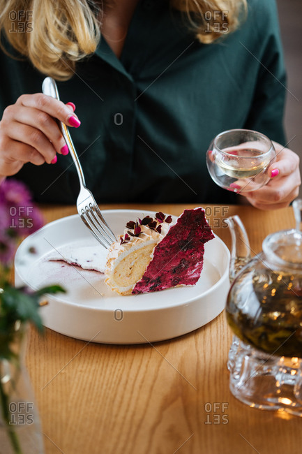 Crop female in dark green blouse sitting at wooden table eating delicious cake with red berries served in white ceramic plate and drinking herbal tea