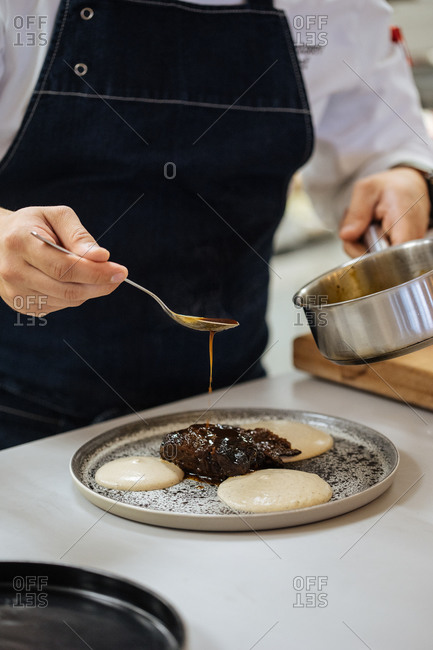 Crop restaurant chef with pot and spoon in hands pouring sauce over food while preparing elegant haute cuisine dish