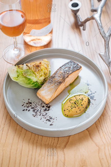 Steamed salmon served with grilled cabbage on white ceramic plate on wooden table with glass and bottle of wine