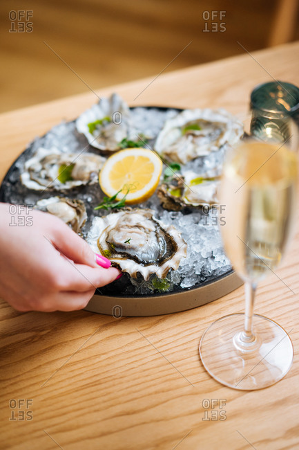 Unrecognizable cropped person with glasses of champagne trying delicious oysters with lemon and herbs in restaurant