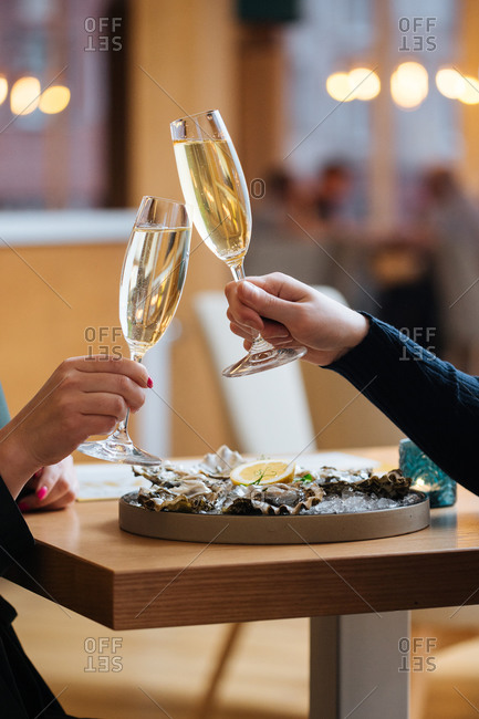 Unrecognizable couple with glasses of champagne trying delicious oysters with lemon and herbs in restaurant