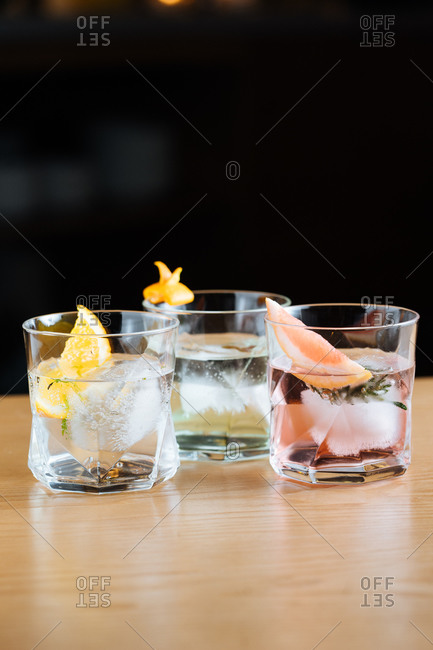 Glass cups with cold alcoholic cocktails with various citruses placed on table against black background