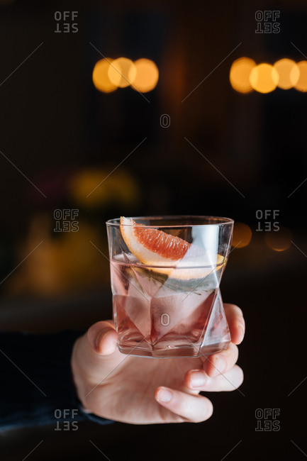 Cropped unrecognizable person hand holding glass with cold alcoholic cocktail with slice of grapefruit and ice cube placed on table against black background