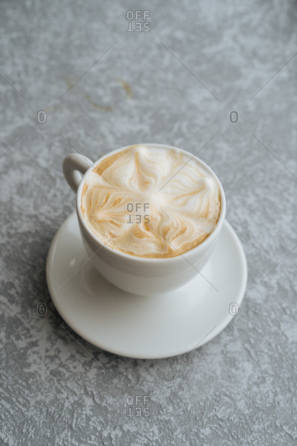 Top view of cup of hot cappuccino with latte art served on white saucer on light grey textured background
