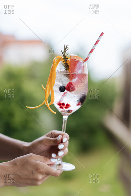Unrecognizable female carrying goblet of cold alcoholic drink with berries and grapefruit decorated with rosemary twig and orange peel
