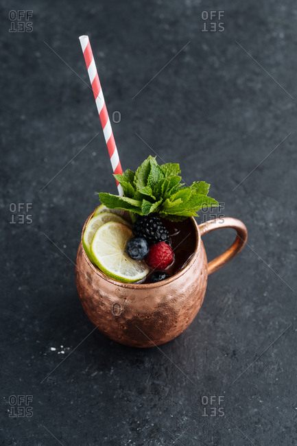 From above metal mug with portion of tasty fruit drink with lime and berries decorated with mint leaves and placed on dark background