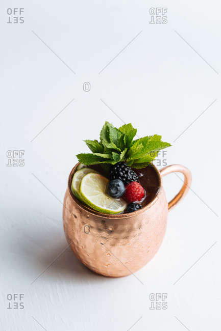 From above metal mug with portion of tasty fruit drink with lime and berries decorated with mint leaves and placed on white background