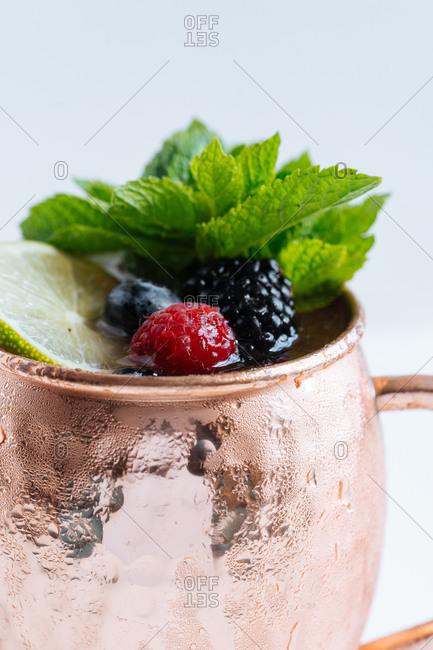 Metal mug with portion of tasty fruit drink with lime and berries decorated with mint leaves and placed on white background