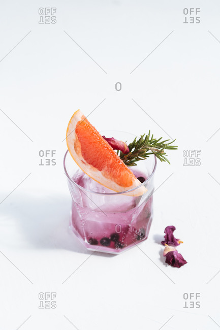 Glass with cold alcoholic cocktail with slice of grapefruit, rosemary, dry blueberry, flowers and ice cube placed on table against white background