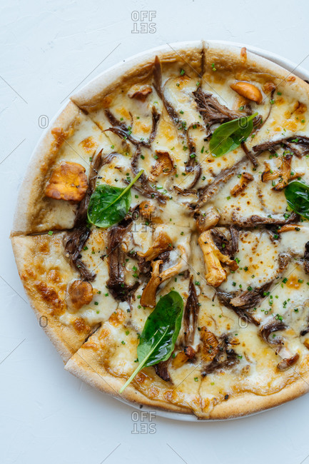 Overhead seafood sliced pizza with mushrooms and basil against white background