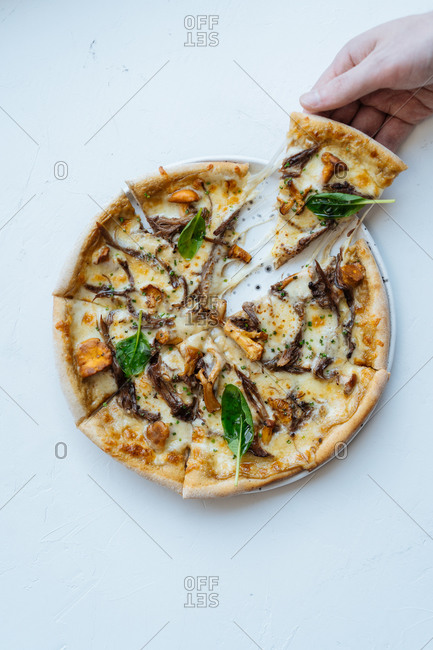 Overhead anonymous person taking slice of palatable seafood pizza with mushrooms and basil against white background