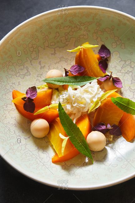 Top view of portion of yummy mango salad with herbs placed on plate on gray tabletop in cafe