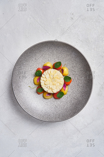 From above delectable fish tartare served with almonds and fresh cherry tomatoes on plate in restaurant
