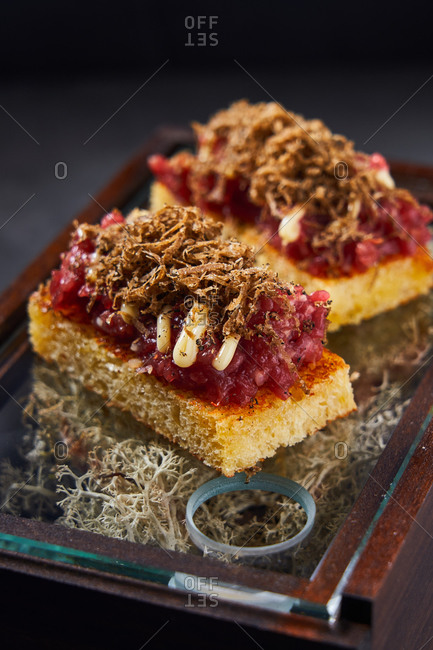 Sweet sponge cake with berry marmalade and chocolate curls placed on box with dry moss