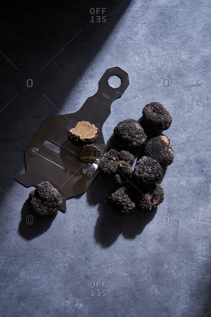 From above bunch of expensive black truffles placed near metal shaver on gray plaster surface