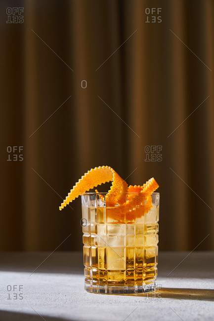 Glass cup with cold old fashioned cocktail with whiskey and orange peel placed on table in bar