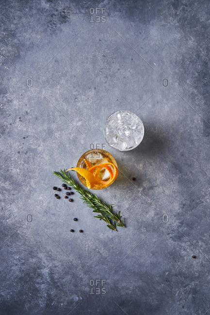 From above top view of glass cup with cold old fashioned cocktail with whiskey and orange peel placed on grey table with rosemary plant a pepper grains