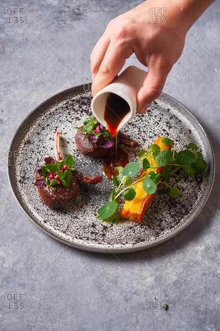 From above cropped unrecognizable person adding sauce to tasty meat medallions with herbs on plate on gray stucco table