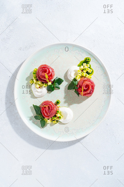 Salmon rolls with onion and herbs served on white ceramic plate on white table background