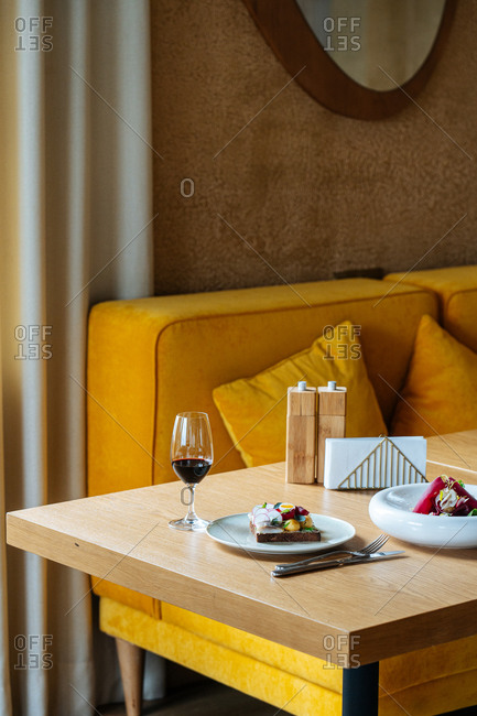 Exquisite dishes and glass of red wine placed on table during dinner in luxury cafe