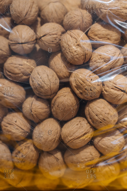 Closeup bunch of ripe walnuts placed inside transparent plastic bag in grocery store