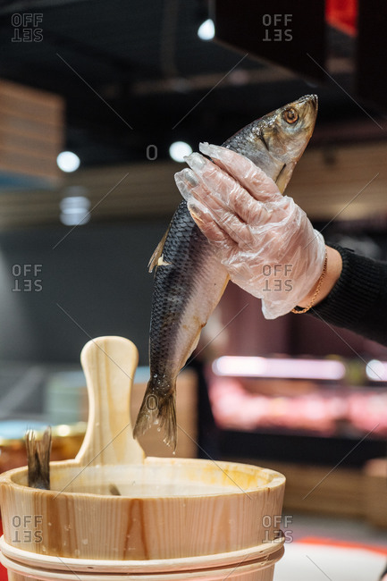 Unrecognizable vendor in glove taking fresh fish from wooden bucket while working in grocery store