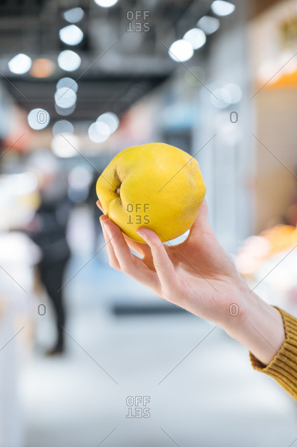 Unrecognizable consumer demonstrating ripe quince on blurred background of modern grocery store