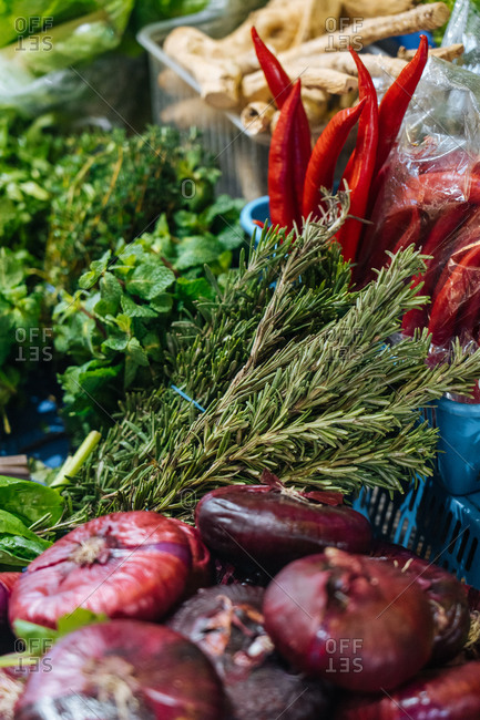 Fresh mint and rosemary placed near red onions and chili peppers on stall in market