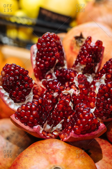 Cute fresh pomegranate placed on heap of fruits on stall in grocery store