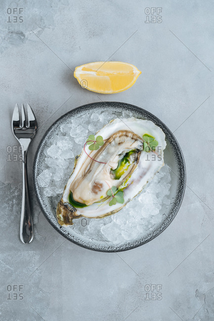 Lemon on delicious oysters on Ice cube on a bowl in a white background in a restaurant