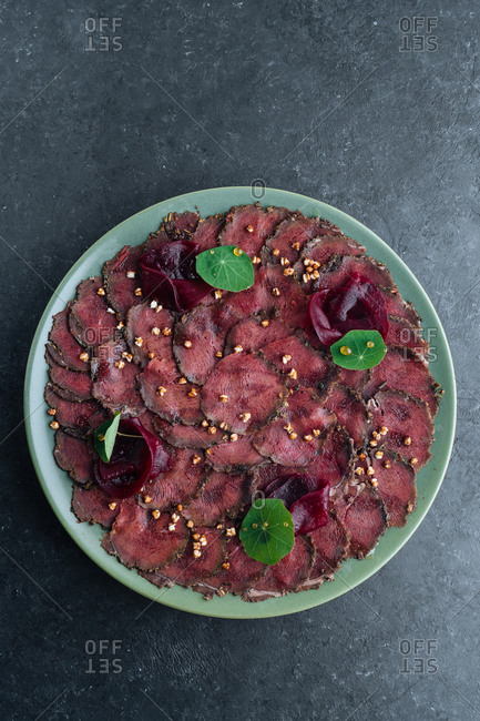 Overhead savory meat carpaccio served with boiled beetroot on plate in restaurant