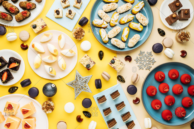 Top view of Christmas baubles and snowflakes placed near plates with various sweet pastry on yellow background