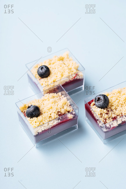 From above glass containers with portions of delicious blueberry dessert placed on blue background