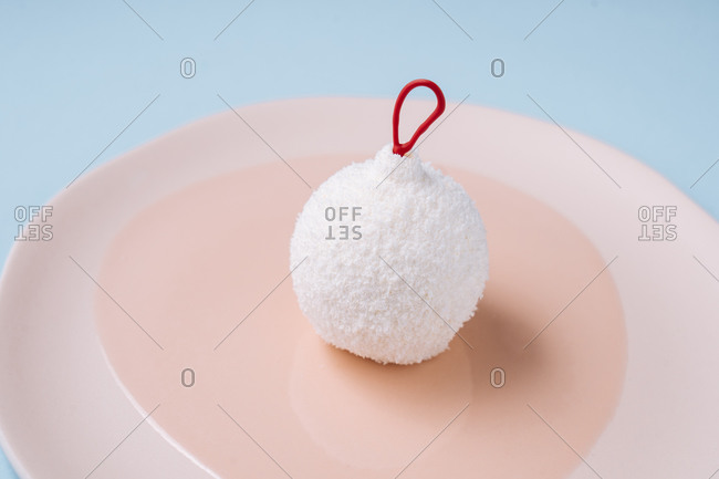Closeup edible bauble with coconut icing placed on plate on blue background during Christmas celebration
