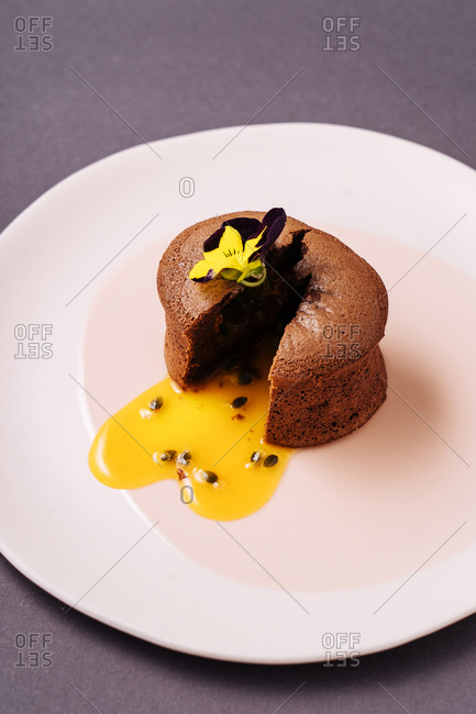 From above cut chocolate muffin with liquid fruit filling and small flower placed on plate