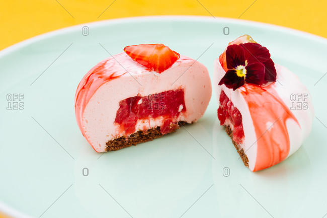 Closeup halves of delicious strawberry pastry with jam filling decorated with flower and placed on plate
