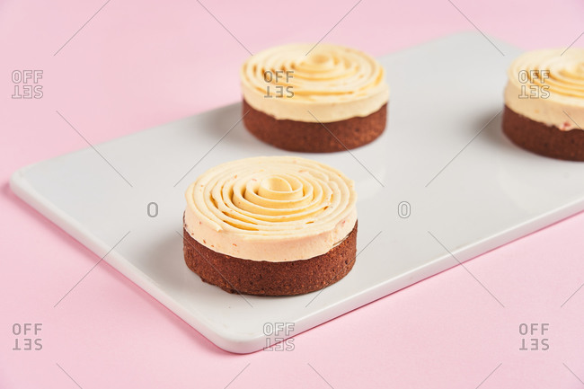 Closeup delicious chocolate pastry decorated with cream spiral and placed on board on pink background
