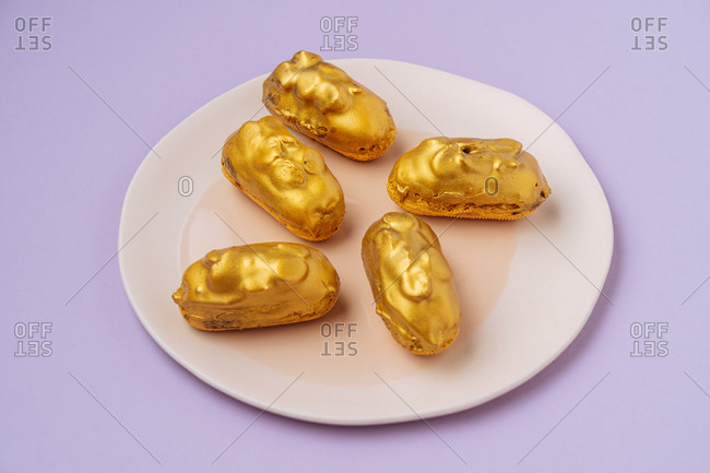 From above small fresh eclairs with golden icing placed on plate on lilac background