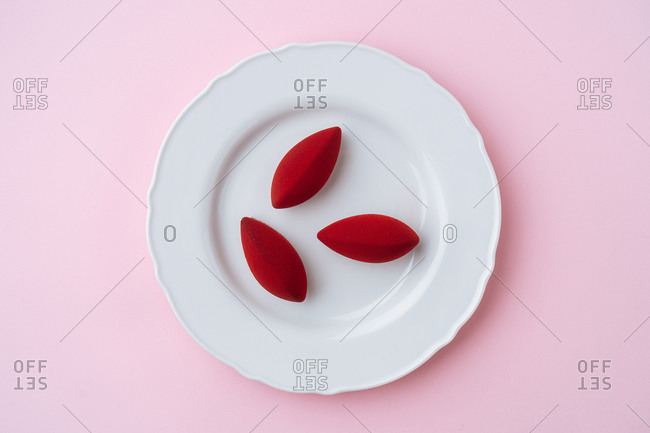 Overhead tasty biscuits with red icing placed on porcelain plate on pink background