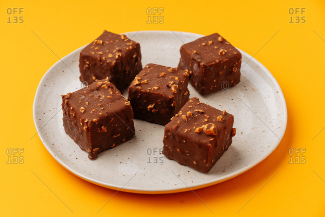 From above yummy cubical biscuits decorated with chocolate frosting and nuts and placed on plate on yellow background