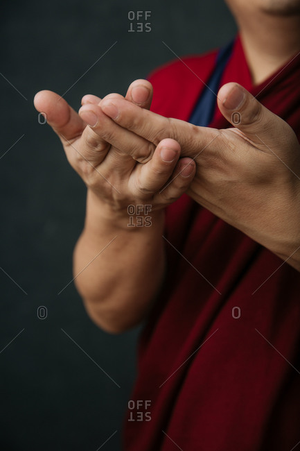 Closeup of hands of crop praying Tibetan monk in traditional red robe with mudra symbolic hands gesture