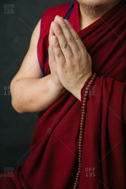 Crop Tibetan monk in traditional red robe with prayer beads and hands folded in Namaste mudra