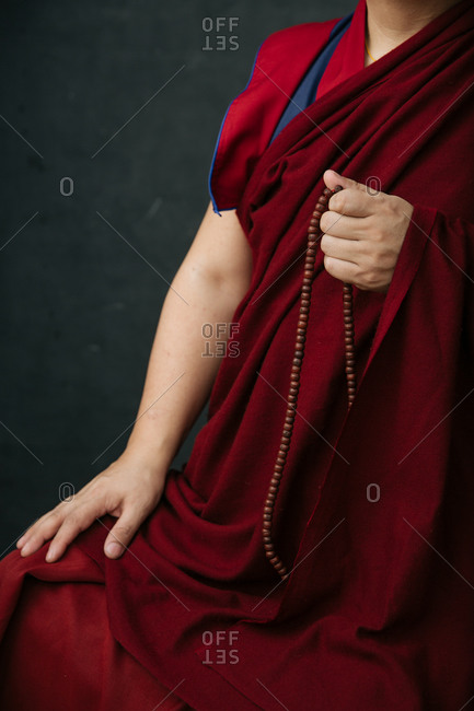 Side view of crop Buddhist monk in traditional red clothes holding prayer beads in hand