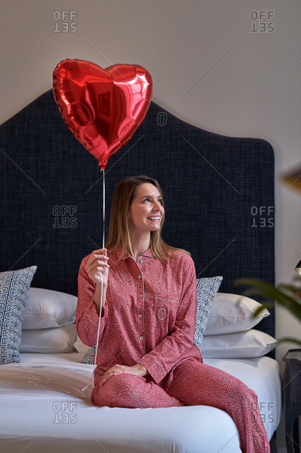 Excited female in pink pajamas looking away with red heart shape balloons and rejoicing while sitting on bed in light modern bedroom