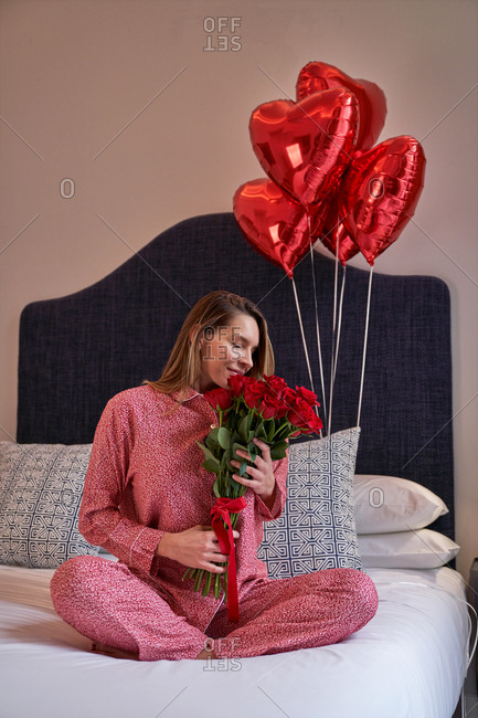 Joyful female in casual clothes sitting on bed against red heart shape balloons and enjoying aroma of fresh roses bouquet in light modern apartment