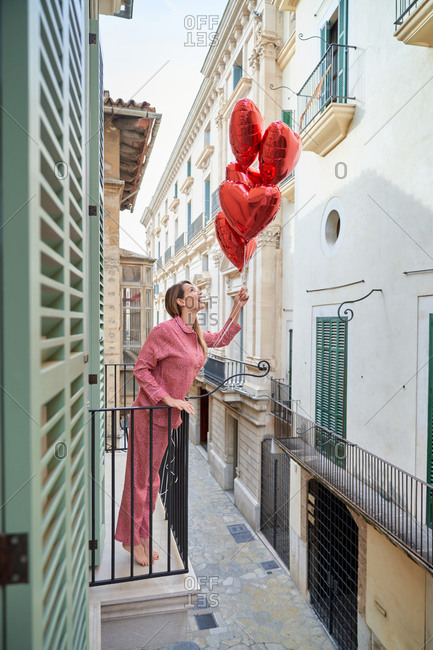 Happy lady in pink sleepwear with vivid red heart shape balloons standing on balcony leaning on metal fence and looking up against facades of buildings in old town