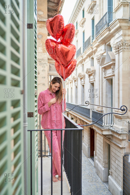 Happy lady in pink sleepwear with vivid red heart shape balloons standing on balcony leaning on metal fence and looking down against facades of buildings in old town